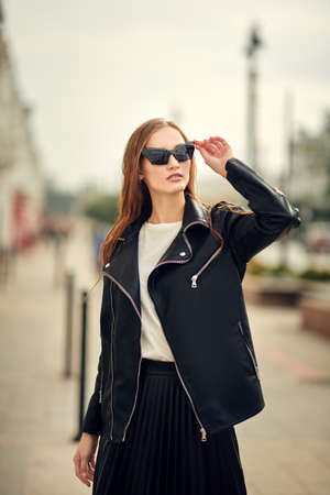 A fashionable lady in sunglasses and black clothes is posing in a city street.