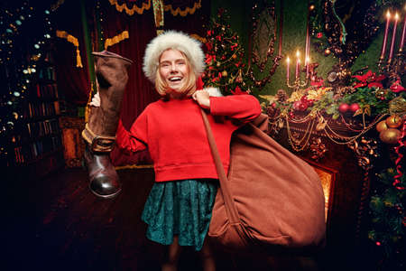 Funny naughty girl holding the boot of Santa Claus with big bag of gifts near fireplace next to the New Year tree. Merry Christmas and Happy New Year! Stock Photo