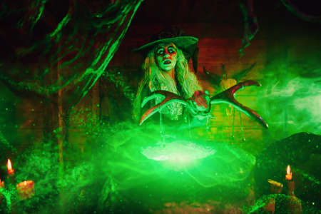 Horrible old witch brews potion in her cauldron with the help of the staff surrounded by magical green light. Halloween. Scary tales.
