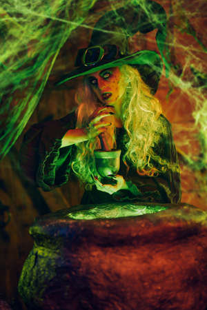 A scary witch is prepared her gruesome lunch in her lair. Halloween. Witchcraft.