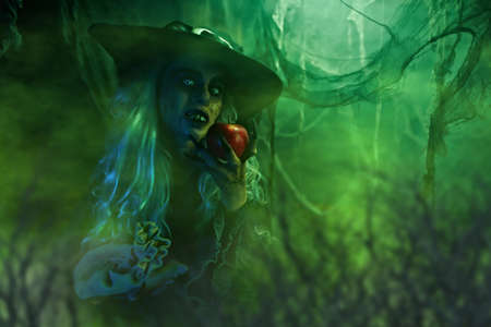 Halloween. Scary old witch holds out a apple. Green smooky background, evil black magic.