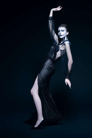 Full length portrait of a beautiful graceful woman with pumpkin skull makeup over black background. Halloween. Day of The Dead.