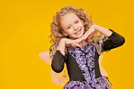 Halloween celebration. Cute little girl with lovely curly hair in a costume of a fairy is smiling at camera. Studio portrait on a yellow background. Copy space. 写真素材