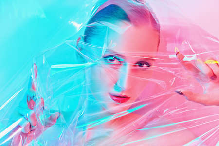 Portrait of a beautiful girl through transparent film in gentle blue and pink lighting. Art beauty concept. Make-up and cosmetics.