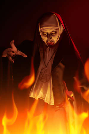 Portrait of evil cursed nun making a threatening gesture on a dark background in light of burning flame. Halloween and Horrors.
