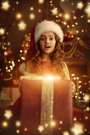 Merry Christmas and Happy New Year! Merry Christmas and Happy New Year! Portrait of a surprised cute girl in red dress and Santa hat holding big gift box in a beautiful Christmas interior.