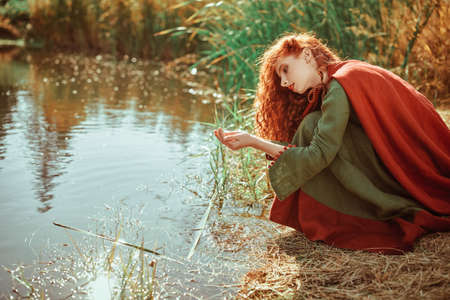 Historical reconstruction of ancient Celtic times. Beautiful red haired girl in a traditional green celtic dress and cape sits by the lake.