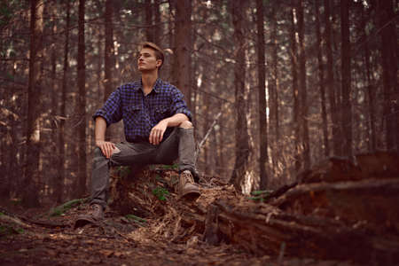 Handsome masculine man in the wild forest. Adventure, spirit of freedom. Active lifestyle.