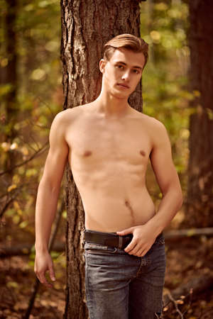 Handsome athletic young man in the wild forest. Outdoor activities and sports. 免版税图像 - 157888007