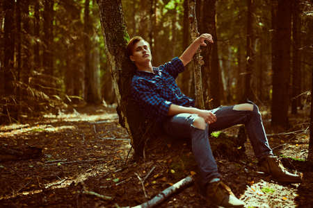 Dreamy guy is relaxing leaning on a tree in the woods. Outdoor recreation.