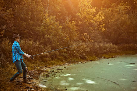 Young man is fishing on the lake on a warm autumn day. Active lifestyle, outdoor recreation. Banco de Imagens