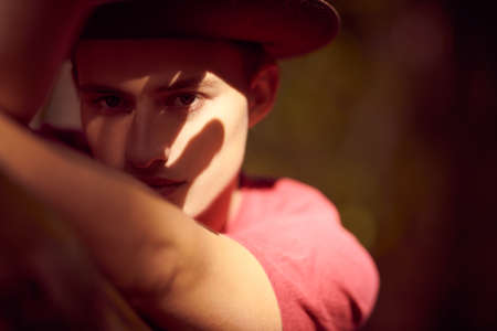 Close-up portrait of a handsome young man in hat in light and shadow. Male beauty. 免版税图像 - 157888015
