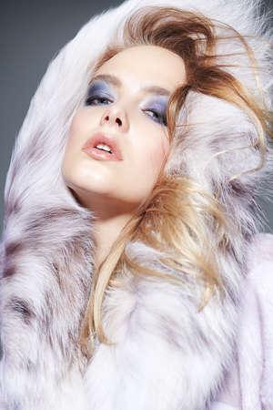 Portrait of a beautiful blonde woman wearing fur coat with fluffy hood. Beauty, winter fashion. Standard-Bild