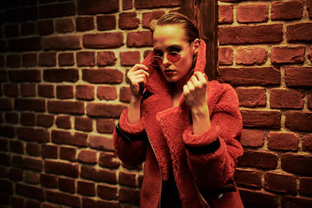 Contemporary young woman in modern red fur coat and sunglasses posing on a brick wall background. Fashion, beauty. Big city style.