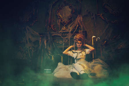 Halloween. Portrait of the dead empress in the old abandoned castle in green haze. Ghost in the castle. Vintage style.