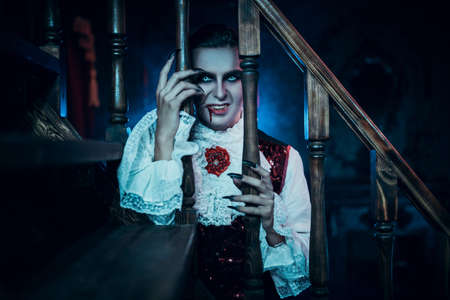 A bloodthirsty vampire aristocrat looks out through the railing on the stairs in the castle. 19th century style. Halloween.