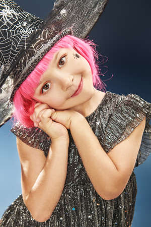 Happy Halloween! Pretty little girl child in witch costume posing on a darl blue background and smiling. Copy space. Banque d'images