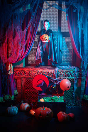 Halloween tales. Scary little boy in vampire costume holding a pumpkin basket is on Halloween night in the old castle.