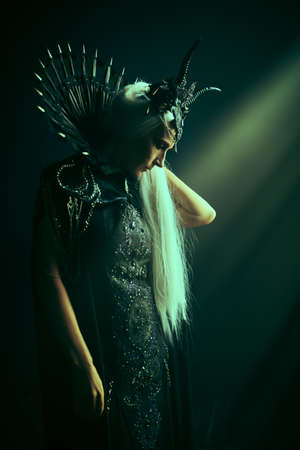Fantasy World. A beautiful majestic black queen, a witch in a rich headdress and a rich black dress, stands in the rays of light in a dark castle.