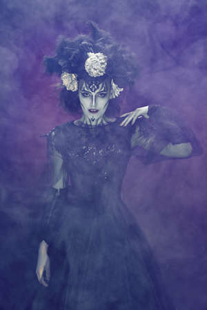 Portrait of a beautiful and scary Calavera Catrina surrounded by a mysterious fog on smoky dark background. Sugar skull makeup and costume. Dia de los muertos. Day of The Dead. Halloween. Stock Photo