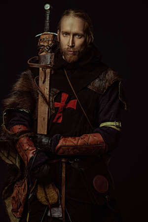 Portrait of a medieval knight in armor and with a sword over black background. Knight Templar. Historical reenactment.