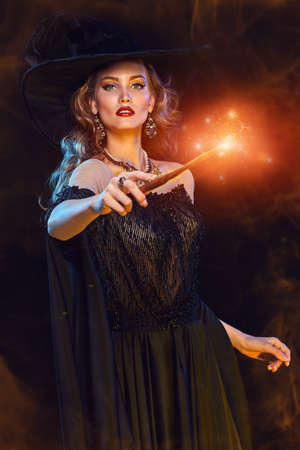 Magic on Halloween. Portrait of an enchanting young woman witch casting with a magic wand. Halloween party, make-up and costume.