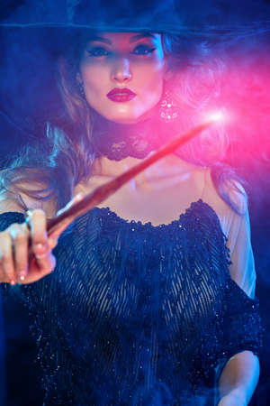 Halloween magic. Portrait of a magnificent young woman witch casting with a magic wand. Halloween party, make-up and costume.