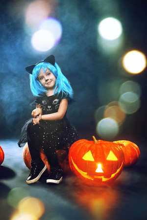 Happy Halloween! Cute little girl child in cat costume posing with pumpkin lantern on a dark background with smoke and lights.