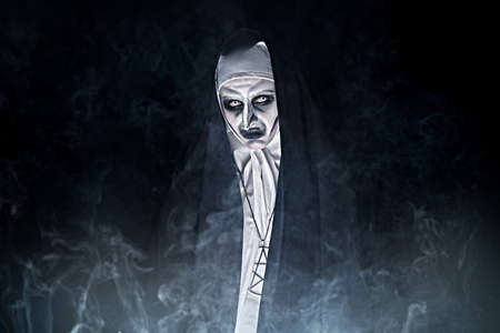 Halloween and horrors. Portrait of a scary devilish nun looking at camera on a black background with mysterious smoke. Copy space.