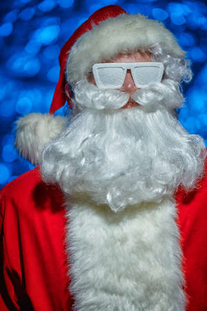 DJ Santa Claus in glasses covered with snow and headphones. Christmas songs and music. Disco lights in the background.
