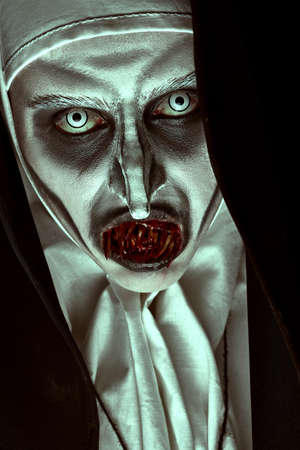 Close-up portrait of a devilish scary nun with bloody teeth. Halloween and Horrors.