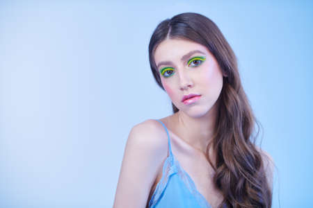 Make-up and cosmetics. Portrait of a beautiful girl with vivid colorful make-up on a blue background. Copy space.