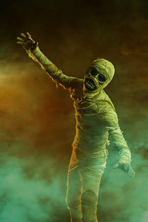 Sinister mummy with black eyes, surrounded by mysterious fog. Halloween. Ancient Egyptian mythology.