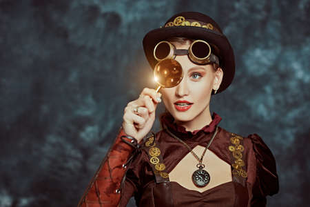 Steampunk concept. Portrait of a beautiful steampunk girl on a grunge background. Copy space.