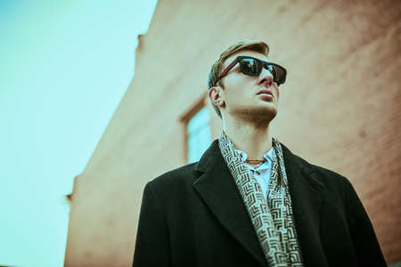 Urban men's style. Handsome man in black sunglasses and elegant black coat stands against the background of the grunge brick houses of the big city. Stock Photo