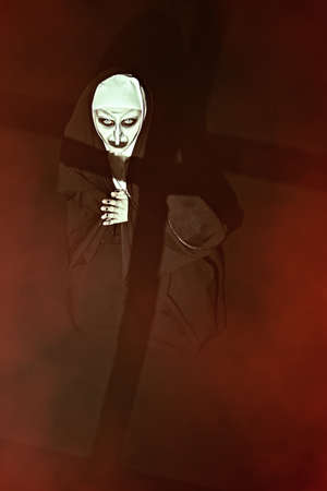 Scary devilish possessed nun with a cross in her hands kneels and prays standing in a dark room. Horrors and Halloween.