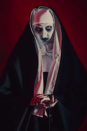 Scary devilish possessed nun with a cross in her hands standing on a bloody red background. Horrors and Halloween.