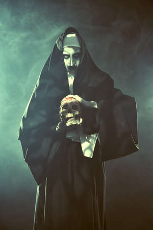 Halloween and Horrors. Devilish evil nun in hellfire with a skull in her hands.
