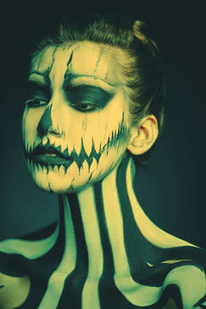Portrait of a beautiful young woman with Halloween skeleton makeup over dark background. Pumpkin queen. Day of The Dead.