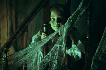 Halloween. Little girl ghost in a nightgown wanders through the old house at night. Stock fotó