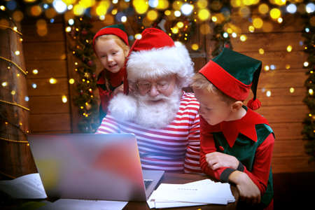 Santa Claus and little elves are sorting mail, reading letters from children. House, workshop of Santa Claus. Stock Photo