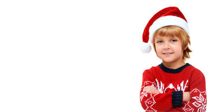 Christmas and New Year concept. Cute little boy in Santa Claus hat smiling at camera. Studio portrait over white background. Copy space.