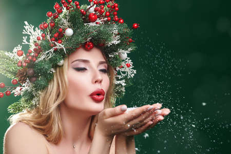 Charming Christmas girl blows snow from palms. Christmas magic atmosphere. Festive pine headdress decorated with Christmas balls, berries and snowflakes. Copy space.