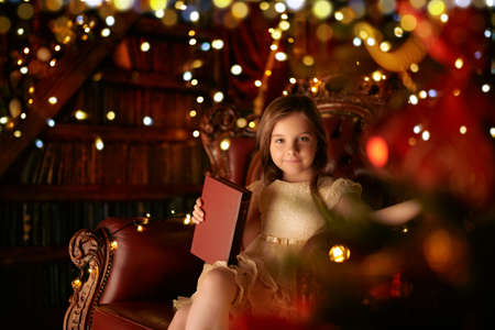 Magic for Christmas. Cute little girl reads fairy tales sitting in a cozy armchair by the New Year tree, surrounded by lights. Christmas Eve.