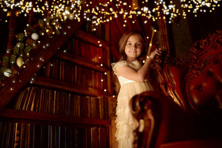 Cute little girl stands by a vintage armchair in a fairy Christmas atmosphere with golden lights. Christmas Eve.