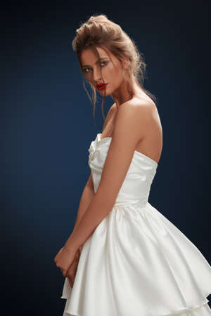 Portrait of a beautiful young bride woman in a fashionable white dress on a dark blue background. Wedding fashion. Make-up and hairstyle.