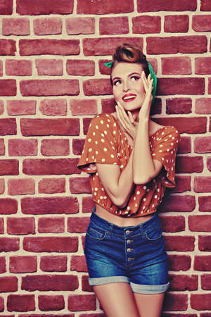 Pin-up girl. Pretty woman dressed in pin-up style, with retro hairstyle and make-up. 版權商用圖片
