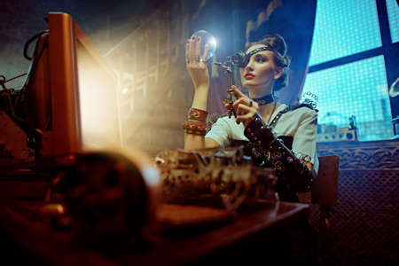 Steampank fantasy world. Beautiful steampunk lady scientist inventor works in her laboratory with Victorian interior. Banque d'images