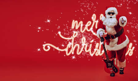 Cool Santa Claus rock musician with electric guitar and in sunglasses on a festive red background. Christmas and New Year party. Archivio Fotografico