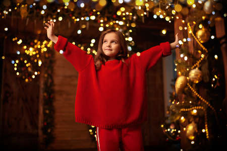 Happy little girl celebrates Christmas in a house beautifully decorated with spruce garlands and New Year's toys. The atmosphere of magic, lights and sparkle is around.